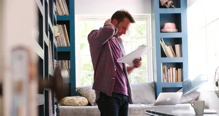adósság : Worried Man Pacing Around Home Office Reading Document