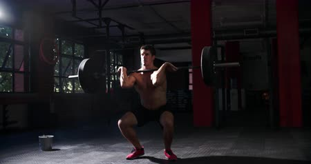 levantamento de pesos : Bare chested man weightlifting barbells in a gym