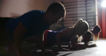 gym : Four people doing press ups at a gym Stock Footage