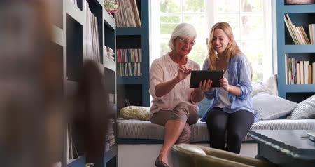 helping : Daughter Helping Senior Mother With Digital Tablet At Home