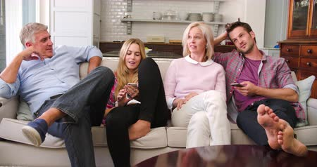 televízió : Parents With Adult Offspring Watching Television At Home