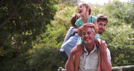 excitação : Slow Motion Shot Of Fathers Giving Children Piggyback Rides Vídeos