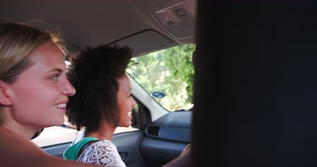 kaland : Friends talking in a car as they drive, view from back seat Stock mozgókép