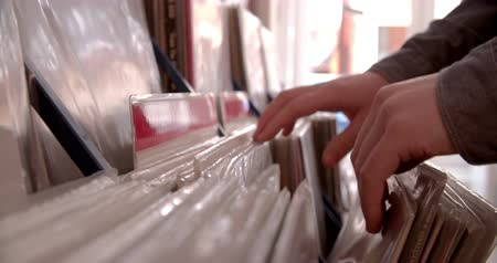 escolha : Close-up of hands sorting through records at a record shop