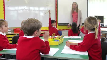interactive table : Pupils Sitting Around Table As Teacher Asks A Question Stock Footage
