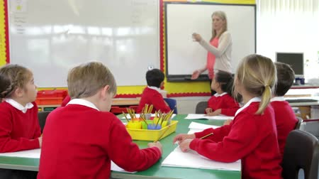 interactive table : Pupils Sitting Around Table As Teacher Stands By Whiteboard Stock Footage