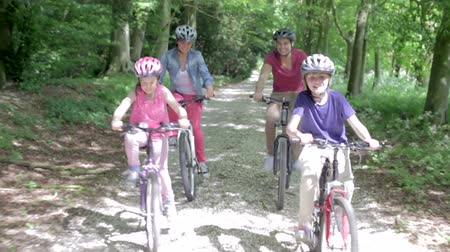 stamboom : Family Riding Mountain Bikes Along Track