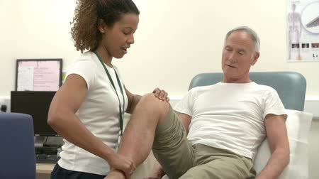 Senior Male Patient Having Physiotherapy In Hospital