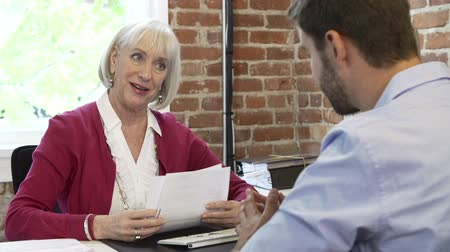 rozhovor : Older Businesswoman Interviewing Younger Man In Office