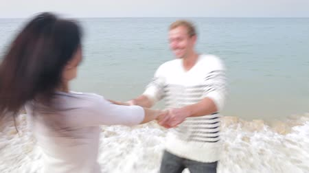 holding steady : Couple Having Fun On Autumn Beach Together Stock Footage