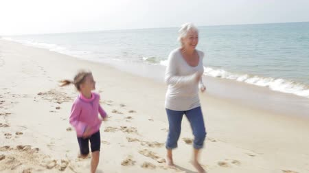 внучка : Grandmother And Granddaughter Running Along Beach Together