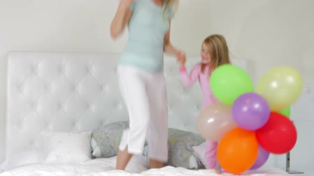 pizsama : Mother And Daughter Jumping On Bed Holding Balloons