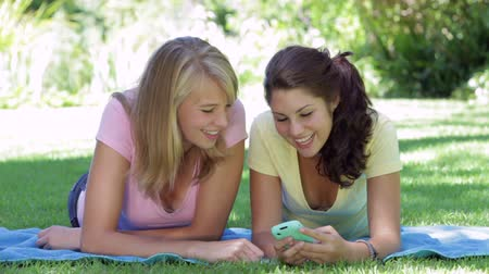 ler : Two Teenage Girls Lying In Garden Reading Text Message