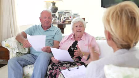 discussão : Senior Couple Sitting On Sofa Talking To Financial Advisor
