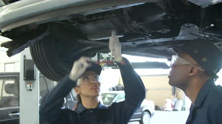 szerelő : Teacher Helping Female Student Training To Be Car Mechanic