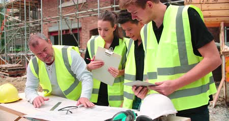 müteahhit : Builder On Building Site Discussing Work With Apprentices Stok Video