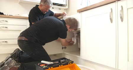 plumber : Plumber teaching apprentice to fix kitchen sink
