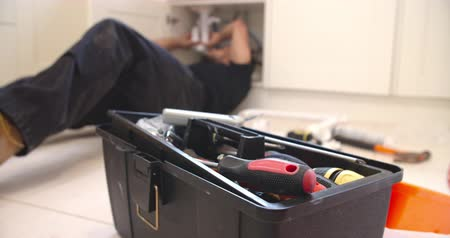 plumber : Plumber fixing sink in kitchen, focus on toolbox