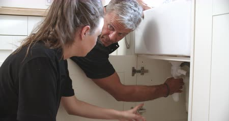 plumber : Plumber teaching female apprentice to fit a sink, close-up