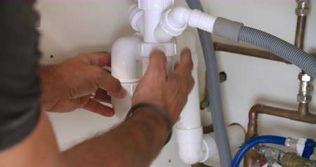 plumber : Male plumber fixing a kitchen sink, close-up of hands
