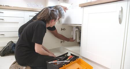 toolbox : Plumber showing female apprentice how to fit a kitchen sink