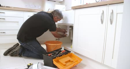 plumber : Middle aged male plumber fixing a kitchen sink