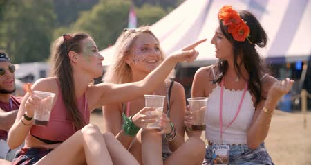 Three female friends sitting on grass at a music festival