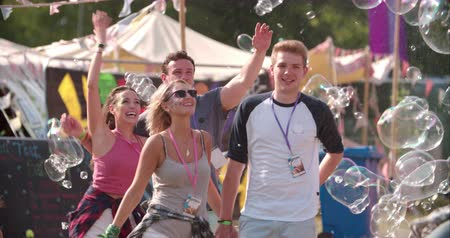 Friends walk through bubbles at music festival, slow motion Stok Video