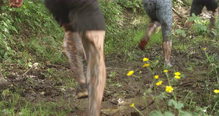 bahno : Legs of competitors running through mud on an assault course