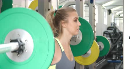 levantamento de pesos : Young woman squat lifting weights at a gym Vídeos