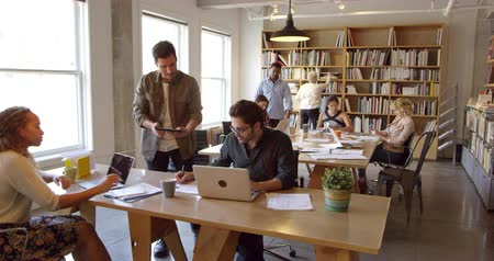 Businesspeople Working At Desks In Busy Office Shot