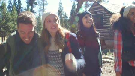 log cabin : Excited friends hiking past a cabin in a forest, close up, shot on R3D Stock Footage
