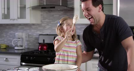 travessura : Girl putting cake mix mix on dad's nose while they bake together, shot on R3D