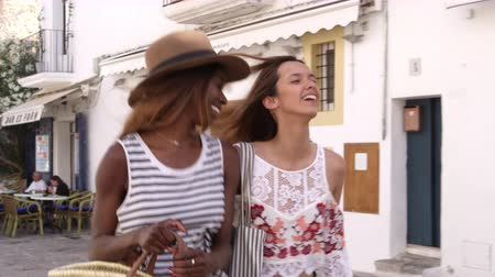 двадцатые годы : Two female friends walking in the streets of Ibiza, Spain, shot on R3D