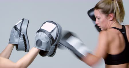 boxer : Female boxer training against mitts of a sparring partner Stock Footage