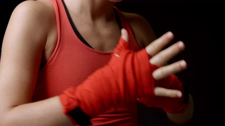 puncs : Female boxer checking her wrapped fists, close-up shot