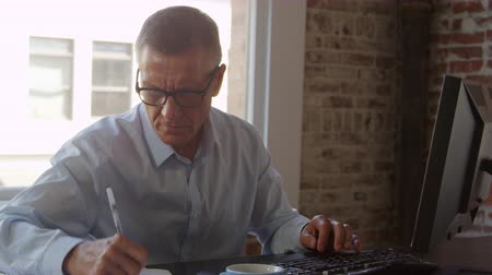 exposed brickwork : Mature Businessman Working On Computer In Office