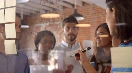 discussion meeting : Businesswoman Writing Ideas On Glass Screen During Meeting Stock Footage