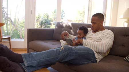 közepes : Father And Son Sitting On Sofa At Home Using Digital Tablet