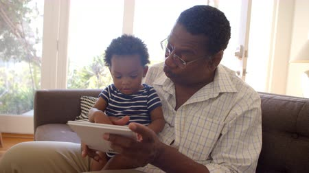 gramotnost : Grandfather And Grandson Reading Book At Home Together