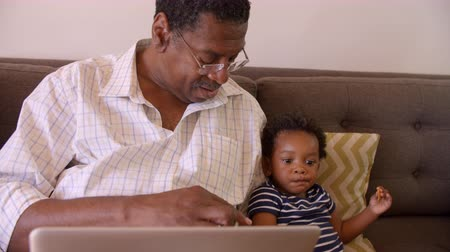 unokája : Grandfather And Grandson Sit On Sofa At Home Using Laptop