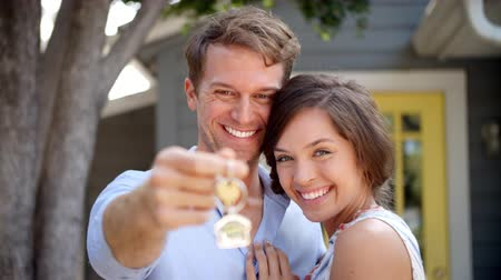 guy home : Portrait Of Happy Couple Standing Outside New Home With Keys Stock Footage