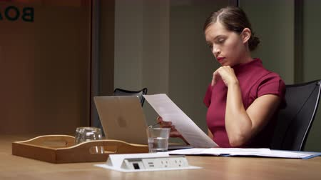 késő : Businesswoman working late on documents in office, close up shot on R3D Stock mozgókép