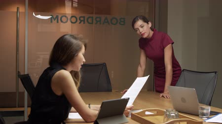 conference table : Two businesswomen working late talking in an office, close up shot on R3D