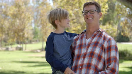 each other : Father carrying seven year old son smiles to camera in park Stock Footage