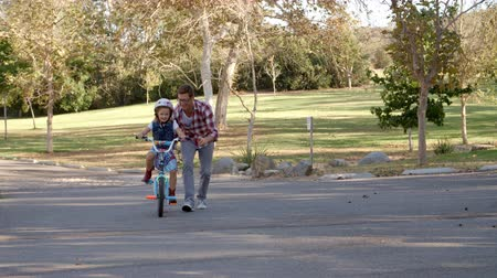 orgulho : Father teaching daughter riding a bike on rural path