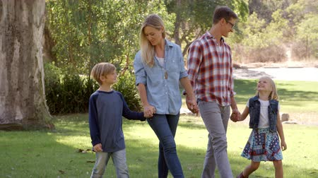 в середине : Young family walk holding hands in a park in the sun, pan Стоковые видеозаписи