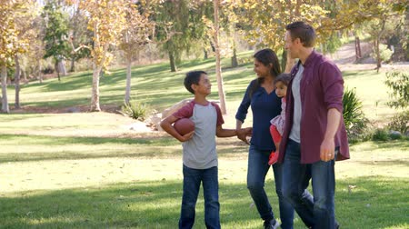 oğlum : Mixed race family walking in a park, front view