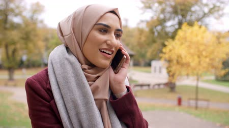 İslamiyet : British Muslim Woman Using Mobile Phone In Park Stok Video