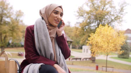 paquistão : British Muslim Woman On Break Using Mobile Phone In Park